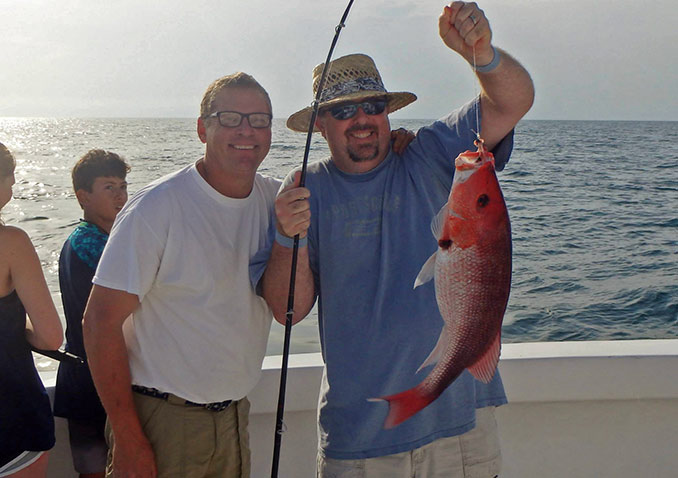Capt Johnny Greene with a smiling father that has just caught him a Snapper